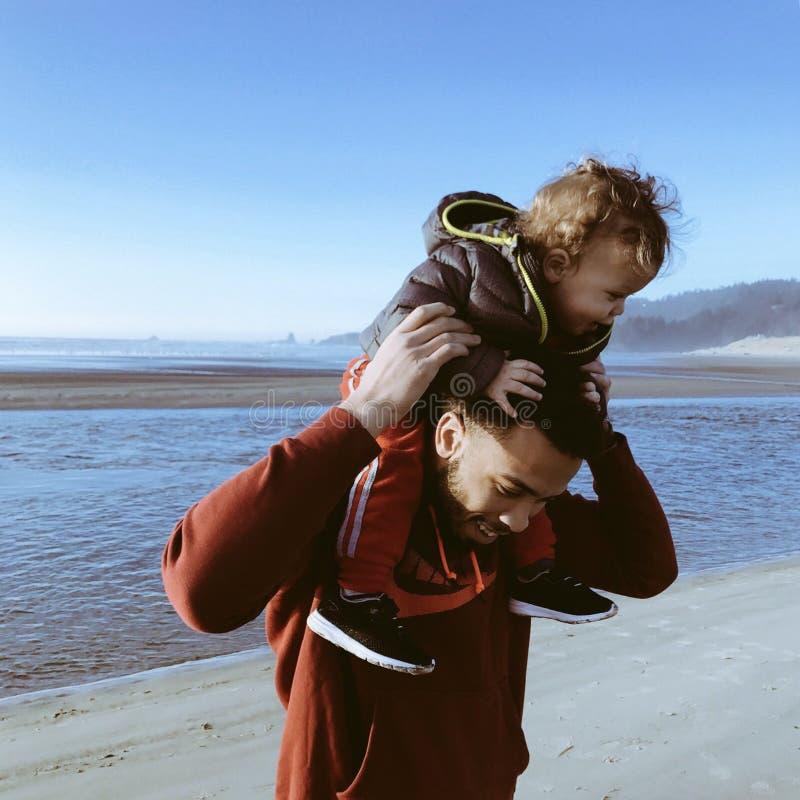 Vader op strand die zijn zoon vervoeren