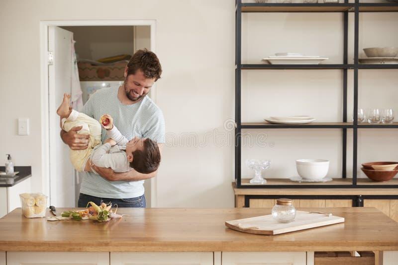 Vader Playing With Son aangezien zij Voedsel in Keuken voorbereiden royalty-vrije stock fotografie