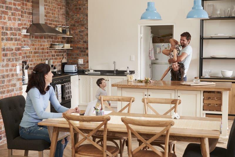 Vader Plays With Children als Moederwerken aangaande Laptop royalty-vrije stock afbeeldingen