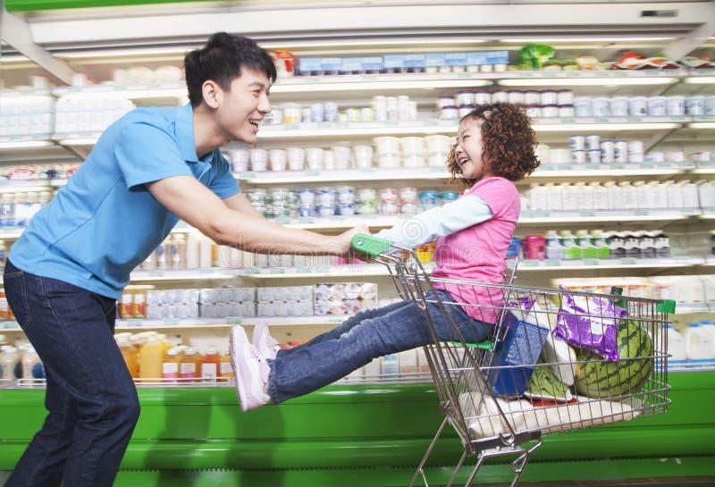 Vader Pushing Daughter in Boodschappenwagentje binnen Supermarkt, het Lachen stock fotografie