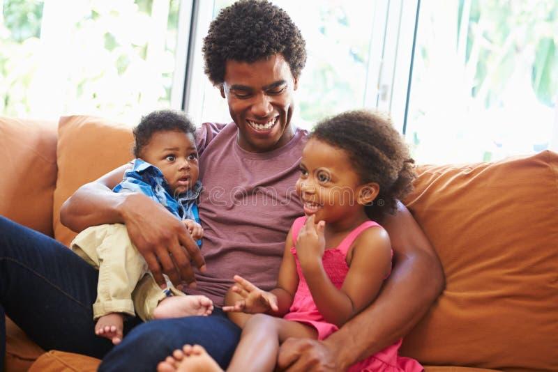 Vader Relaxing On Sofa With Young Children stock afbeeldingen