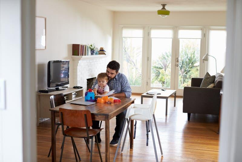 Vader Sits At Table en Spelen met Babyzoon thuis royalty-vrije stock foto
