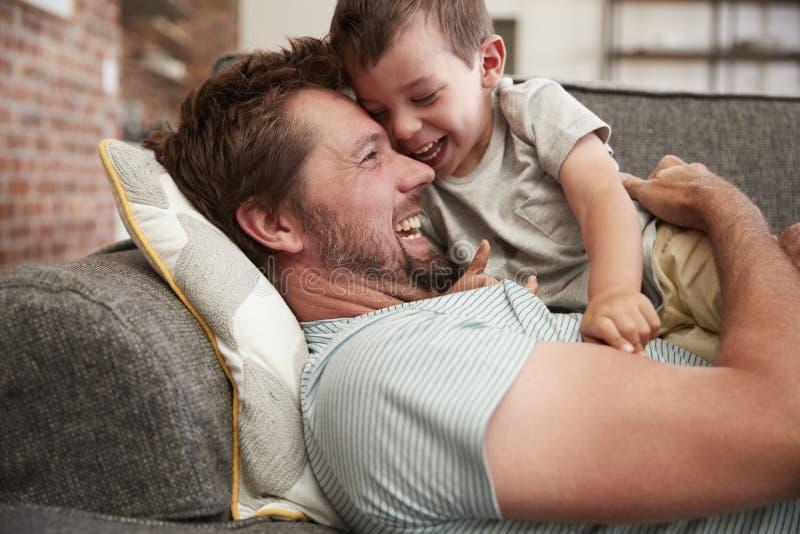 Vader And Son Cuddling op Sofa Together royalty-vrije stock foto