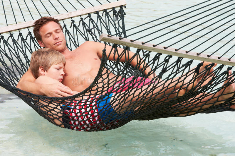 Vader And Son Relaxing in Strandhangmat royalty-vrije stock foto's