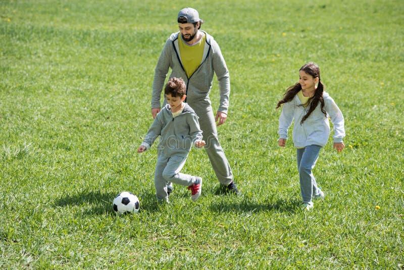 vader speelvoetbal met kinderen op gras stock fotografie