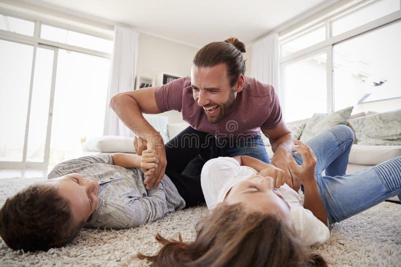 Vader Tickling Children As spelen zij Spel samen in Zitkamer royalty-vrije stock afbeelding