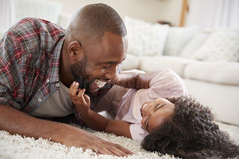 Vader Tickling Daughter As spelen zij Spel samen in Zitkamer royalty-vrije stock fotografie