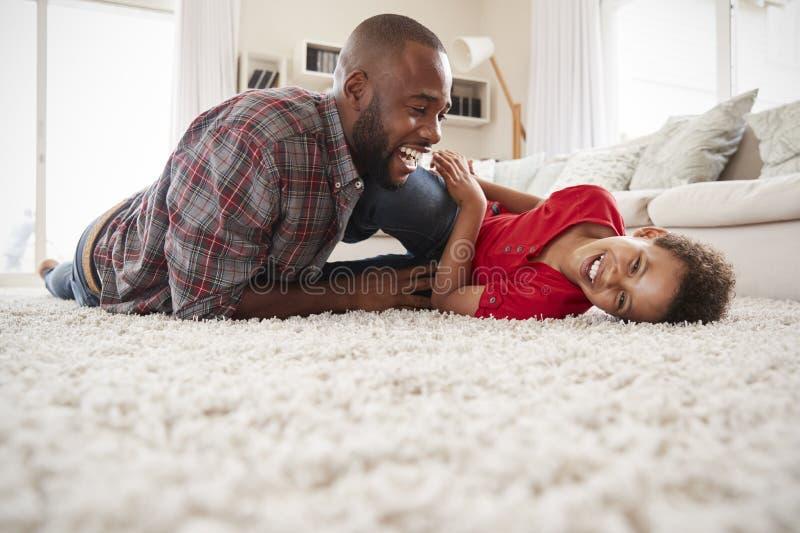 Vader Tickling Son As spelen zij Spel samen in Zitkamer stock afbeeldingen