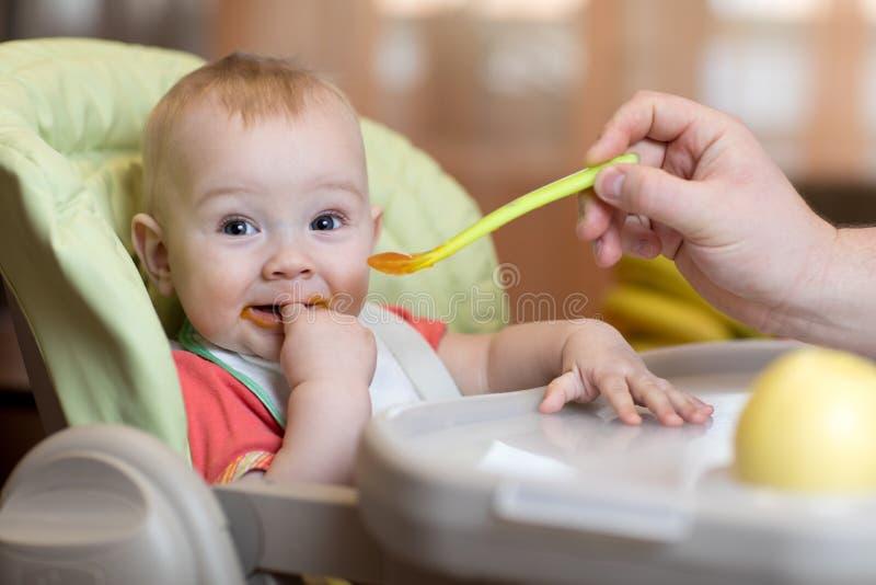 Vader voedende baby met lepel stock fotografie