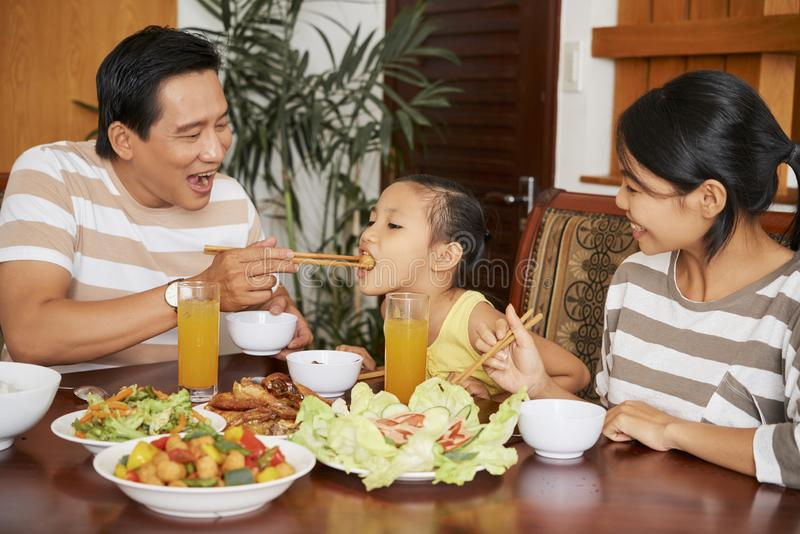 Vader voedende dochter bij diner stock afbeeldingen