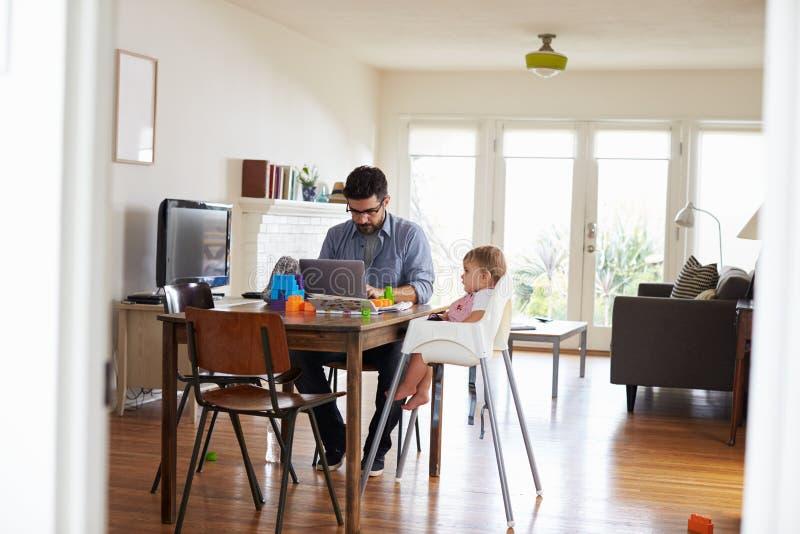 Vader Works On Laptop als Spelen van de Babyzoon met Speelgoed stock afbeeldingen