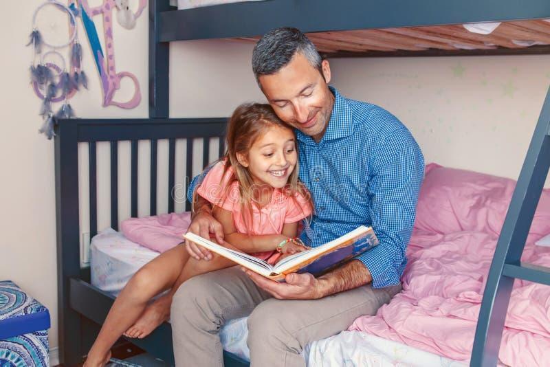 Vaderpapa en dochtermeisje die thuis boek lezen royalty-vrije stock afbeelding