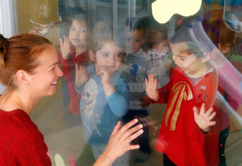 Vaders en zonengebaar tussen het glasvenster in een peuterkleuterschool royalty-vrije stock foto's