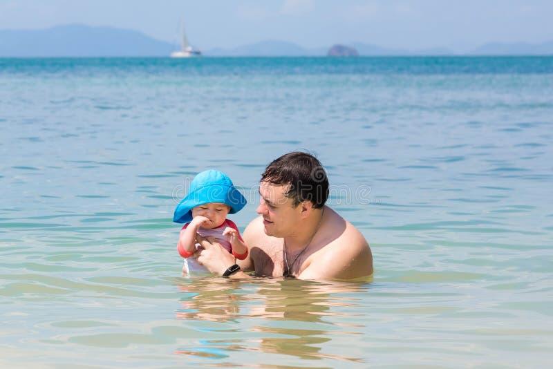 Vaderspelen met zijn dochter in het water op zee Het babymeisje krijgt tandjes stock foto