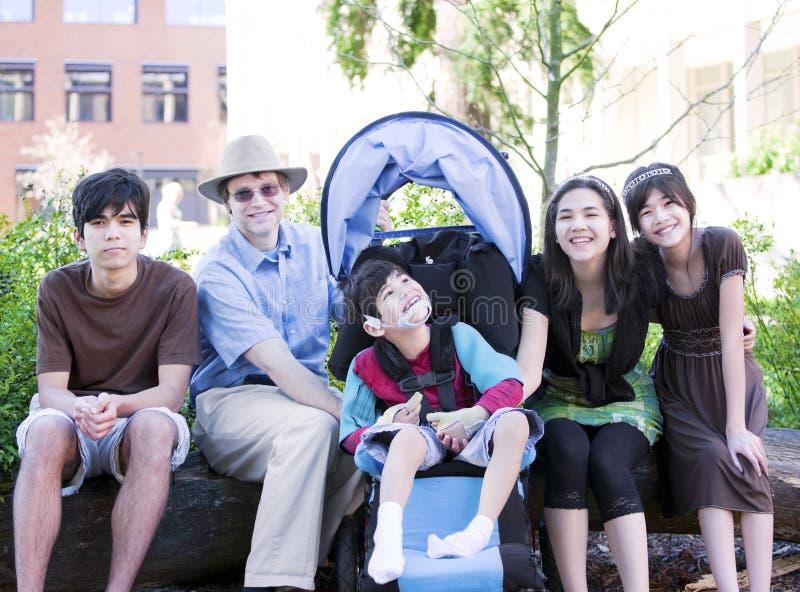 Vaderzitting met zijn biracial kinderen en gehandicapte zoon stock fotografie