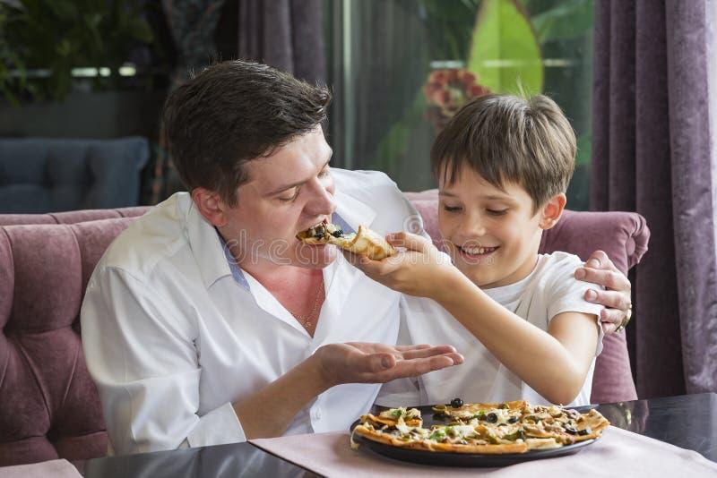 Vaderzoon die een Italiaanse pizza eten royalty-vrije stock foto