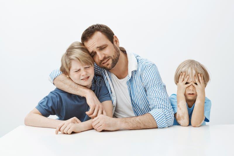 Vaderzorg met zonen terwijl het zitten bij lijst, het koesteren van jongen en schreeuwen die, en ongelukkig terwijl jongere zoon  royalty-vrije stock foto