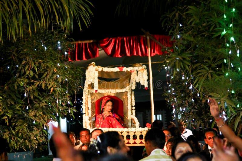 Vadodara, Индия - 20-ое июля 2018: невеста входит в традиционное индусское место свадьбы вечером с толпой ожидания семьи и друзей стоковое фото