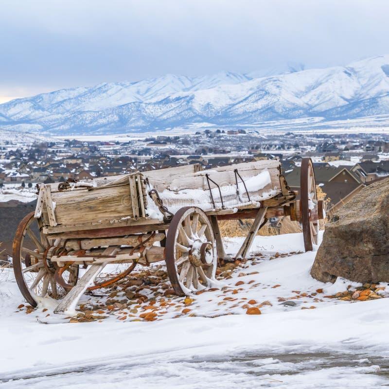 Vagão de madeira rústico do quadrado ao lado de uma rocha enorme sobre um monte nevado no inverno imagens de stock