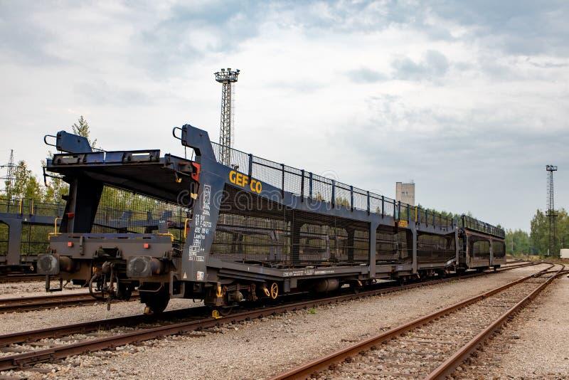 Vagão descarregado do trem para transportar os carros novos que esperam em uma trilha de estrada de ferro fotos de stock royalty free
