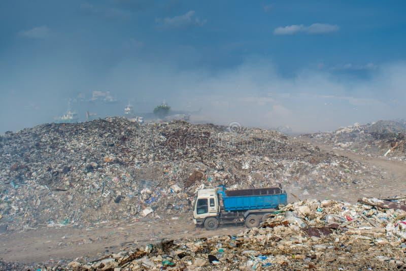 Vagão do automóvel na descarga de lixo enorme completamente do fumo, da maca, de garrafas plásticas, de desperdícios e de lixo na foto de stock royalty free