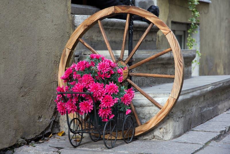 Vagão florescido com a roda velha antiga imagens de stock