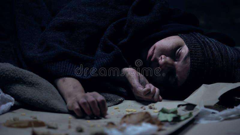 Vagabondo senza tetto che dorme sulla via in pieno di immondizia, povert?, insicurezza sociale immagine stock