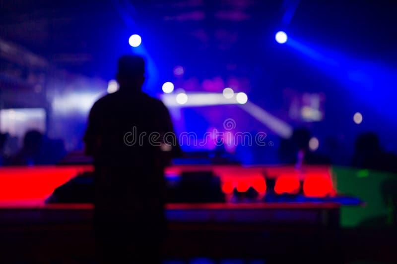 Vage achtergrond: Club, disco die DJ en muziek voor menigte van gelukkige mensen spelen mengen Nachtleven, overleglichten stock afbeeldingen