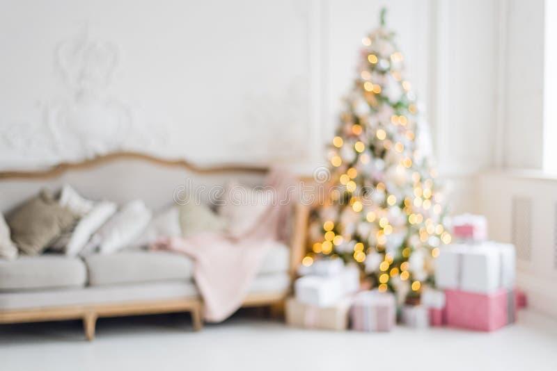 Vage achtergrond Het binnenland van de luxewoonkamer met bank verfraaide elegante Kerstboom, giften, plaid en hoofdkussens stock foto's