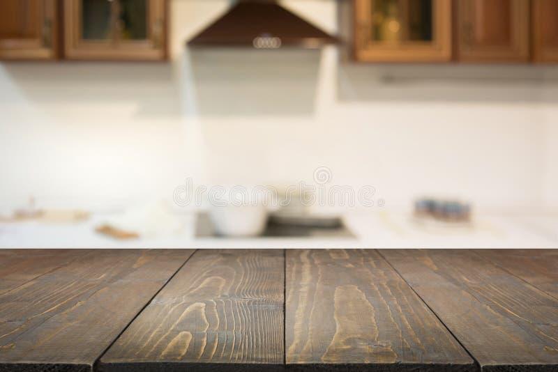 Vage achtergrond Het lege houten tafelblad en defocused moderne keuken voor vertoning of montering uw producten royalty-vrije stock foto