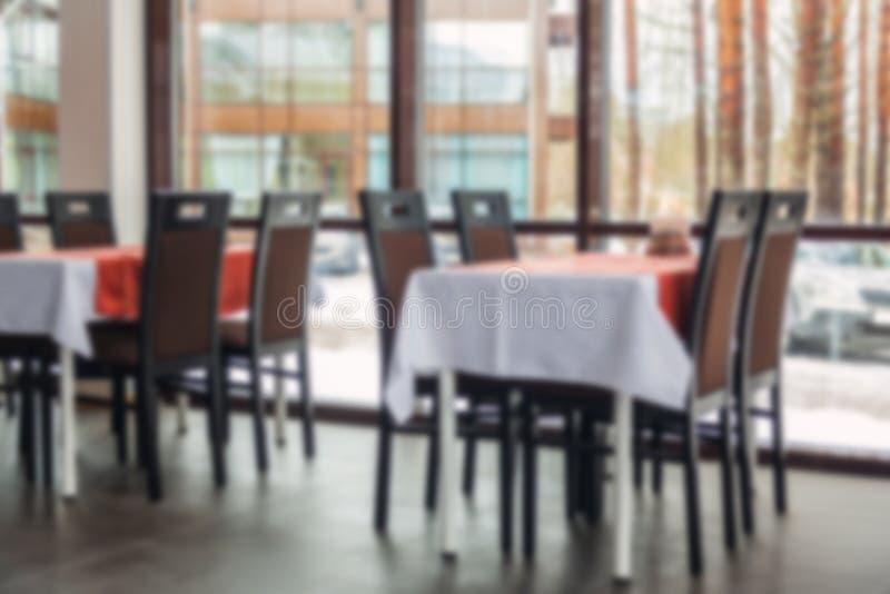 Vage Achtergrond van eettafels en stoelen in het restaurant Licht binnenland stock afbeelding