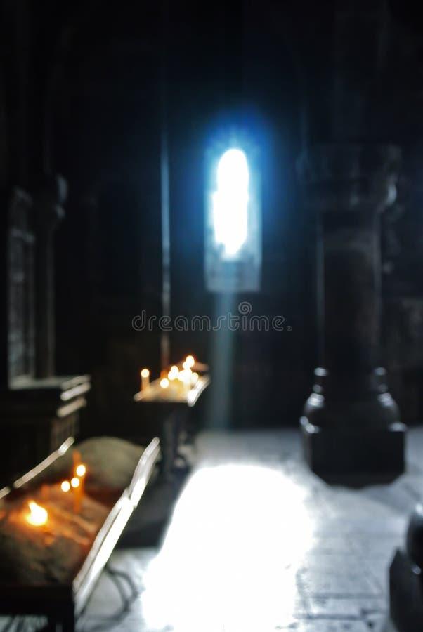Vage achtergrond van het oude Armeense christelijke binnenland van het kerkklooster met een zonstraal die aan de kaarsen van een  royalty-vrije stock afbeeldingen