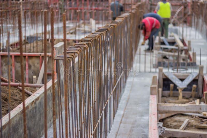 Vage arbeiders en staalversterking in stichting van nieuwe bu royalty-vrije stock foto