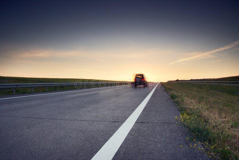 Vage auto bij hoge snelheid op de weg bij zonsondergang stock afbeeldingen