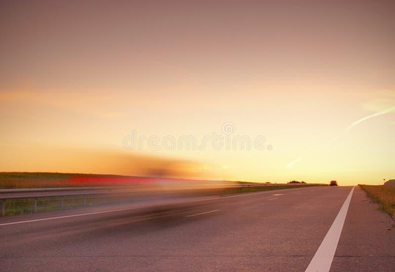 Vage auto bij hoge snelheid op de weg bij zonsondergang stock foto