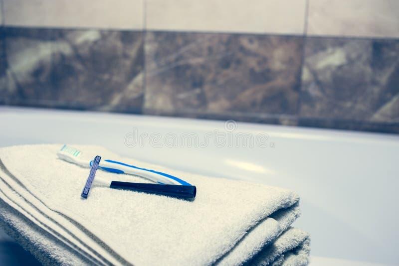 Vage badkamers binnenlandse achtergrond en witte kuuroordhanddoeken op Marmeren Tandenborstelscheermes stock fotografie