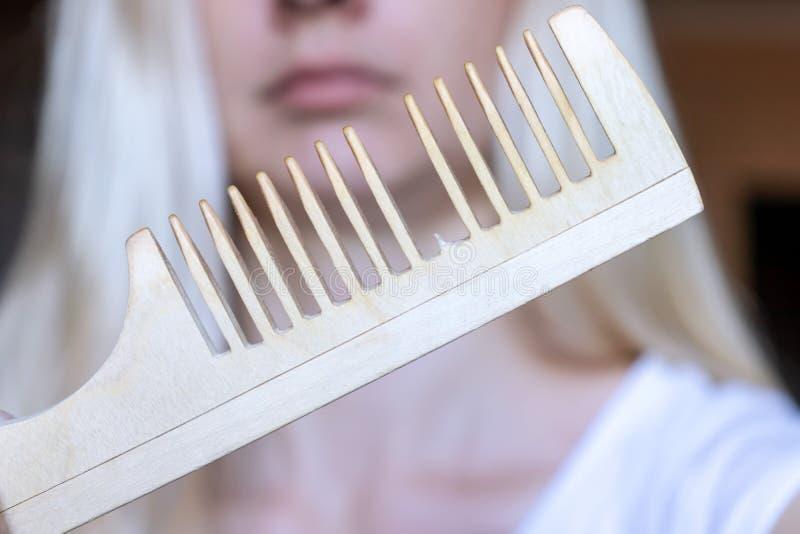 Vage blonde vrouw met een gebroken kam in haar hand royalty-vrije stock foto