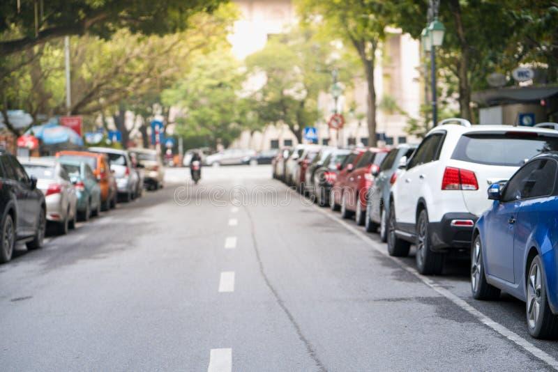 Vage die auto's aan de stedelijke straatkant worden geparkeerd royalty-vrije stock fotografie