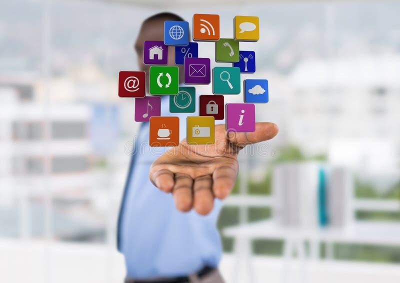 (vage die) zakenman met hand van met toepassingspictogrammen over wordt uitgespreid Vage bureauachtergrond stock foto's