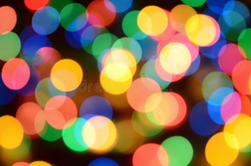 Vage feestelijke kleurrijke lichten over zwarte nuttig als achtergrond Alle hoofd inbegrepen kleuren Rood, geel, groen en blauw stock foto's