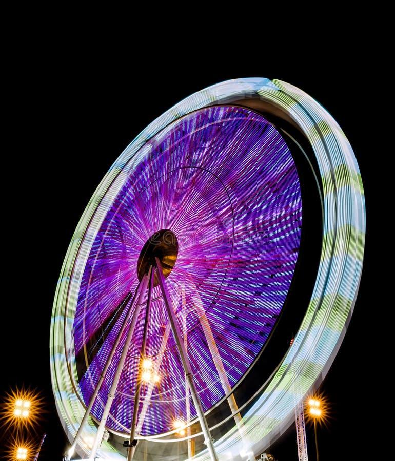 Vage ferris rijden bij nacht in een park van afleiding met mooie kleuren stock afbeelding