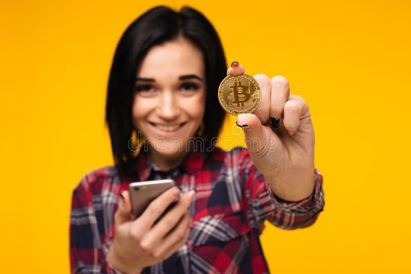 Vage glimlachende vrouw die een Bitcoin in haar hand houden en het tonen stock afbeeldingen