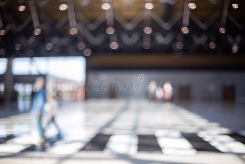 Vage mooie bokehachtergrond: de vage mensen, reizigerssilhouet lopen in de zaal van het luchthavenvertrek stock afbeelding