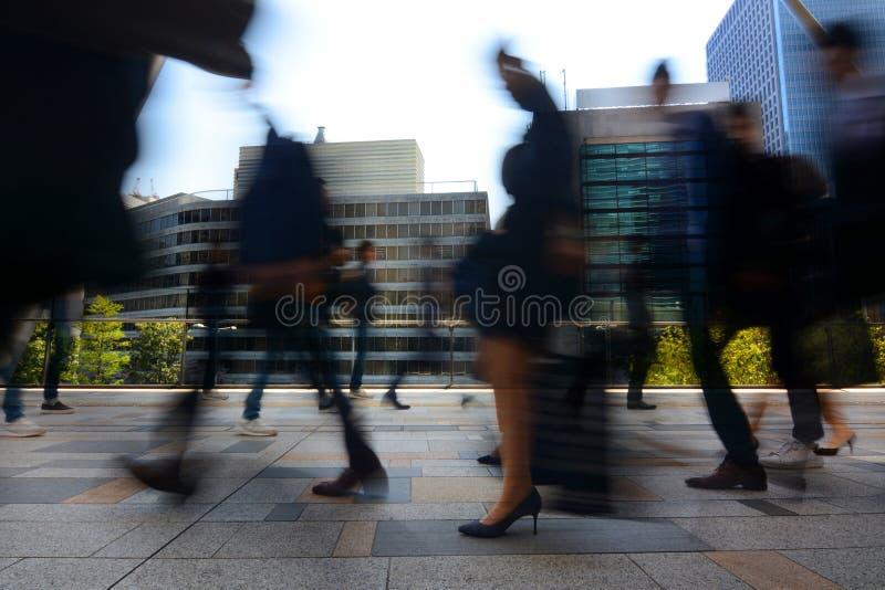Vage motie van zakenlieden en onderneemsters die aan het werk tijdens bezig spitsuur in Tokyo, Japan omzetten stock afbeeldingen