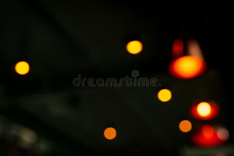 Vage rode, oranje en gele bokeh abstracte achtergrond Onduidelijk beeld bokeh op donkere achtergrond Straatlantaarneffect met moo royalty-vrije stock afbeelding