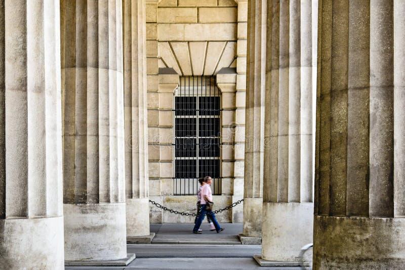 Vage silhouetten van toeristen die onder de reusachtige majestueuze kolommen van het oude gebouw lopen royalty-vrije stock foto