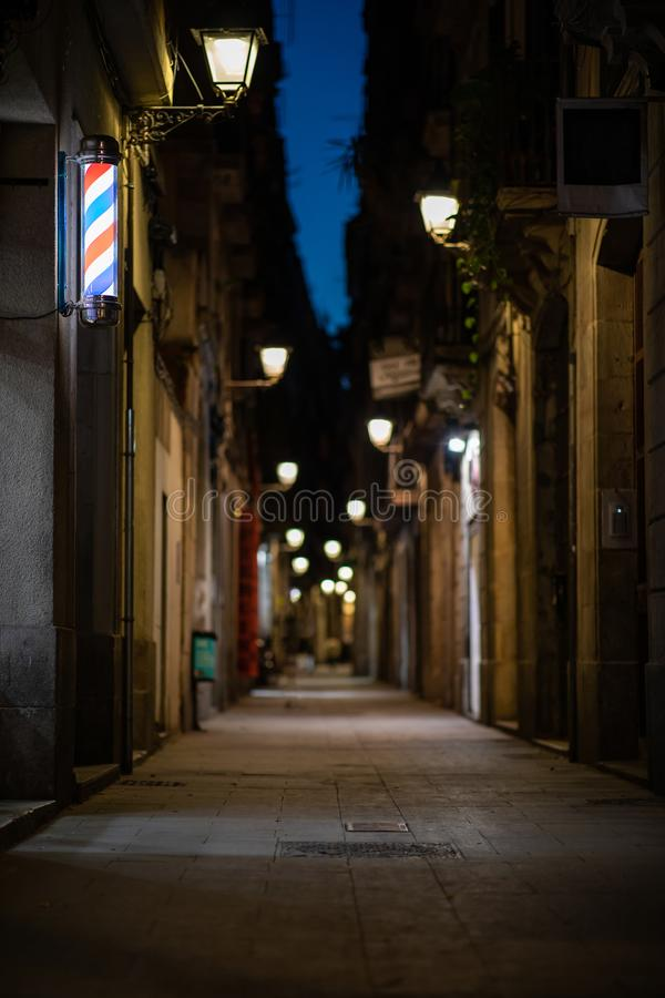 Vage steeg van de binnenstad bij nacht met herenkapper of hairdresser& x27; s teken op de muur stock afbeeldingen