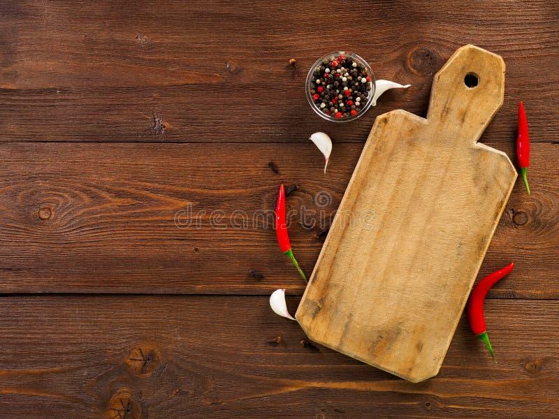 Vagens encarnados da pimenta de pimentão e ervilhas, placa de corte, cravo-da-índia de alho fotos de stock