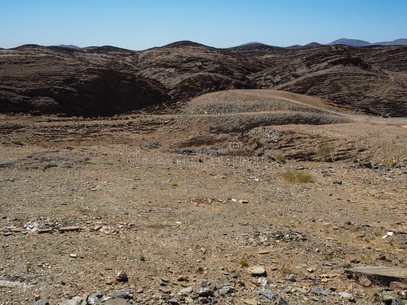 Vagga bakgrund för landskapet för bergtexturfoder av unik geografi för den Namib öknen med blixtrande stenjordning och ökenväxten arkivbild