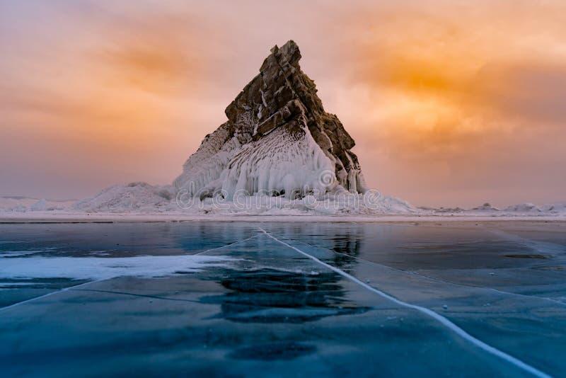 Vagga berget på att frysa vattensjön med solnedgånghimmelbakgrund arkivbilder